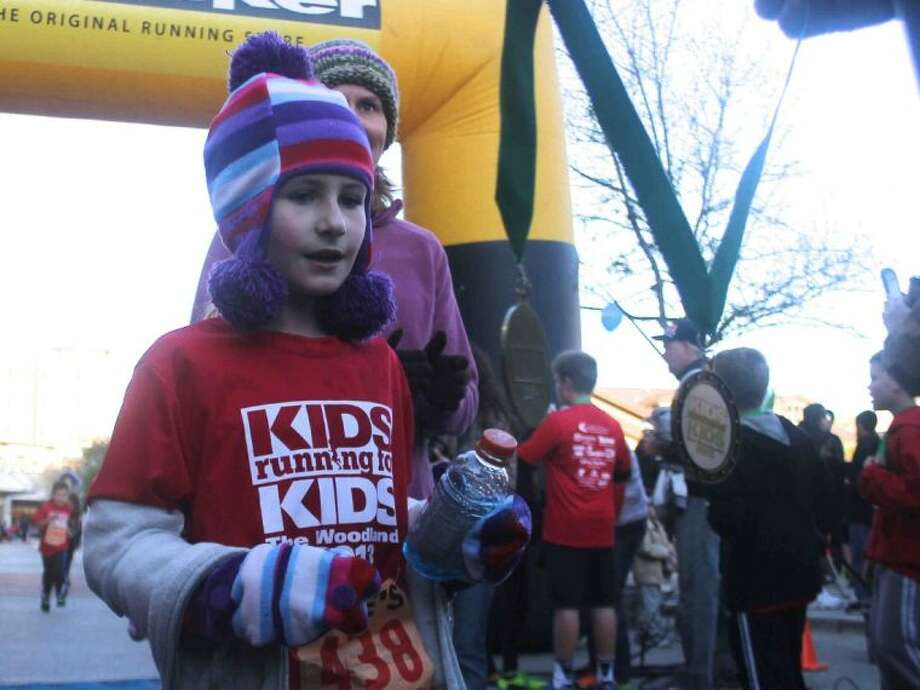 Aubrie Edmondson gets a medal after finishing the inaugural Kids Running for Kids race benefiting Conroe ISD at Market Street in The Woodlands Saturday. Photo: Jason Fochtman