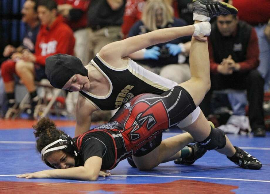 Conroe's Alex Powell, top, tangles with Abril Ramirez of El Paso El Dorado during the second round of the girls 128-pound class at the UIL State Wrestling Tournament at Austin ISD's Delco Center on Friday. Powell lost the match when Ramirez pinned her at the 5:51 mark.