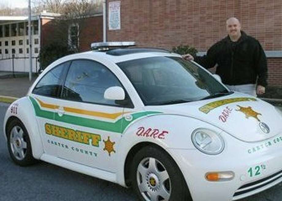 In this Feb. 9, 2012 photo, Carter County Deputy Shane Watson poses with his Volkswagen beetle in Elizabethton, Tenn. A Volkswagen beetle owned by the Carter County Sheriff's Department became an improvised pursuit vehicle — at about 20 mph. The beetle won. (AP Photo/The Johnson City Press, John Thompson)