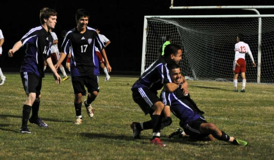 Willis' Christian Juarez is mobbed by teammates after scoring a goal against Caney Creek during the 2011 season. Jaurez was recently named the District 39-4A Most Valuable Player. Photo: Keith MacPherson