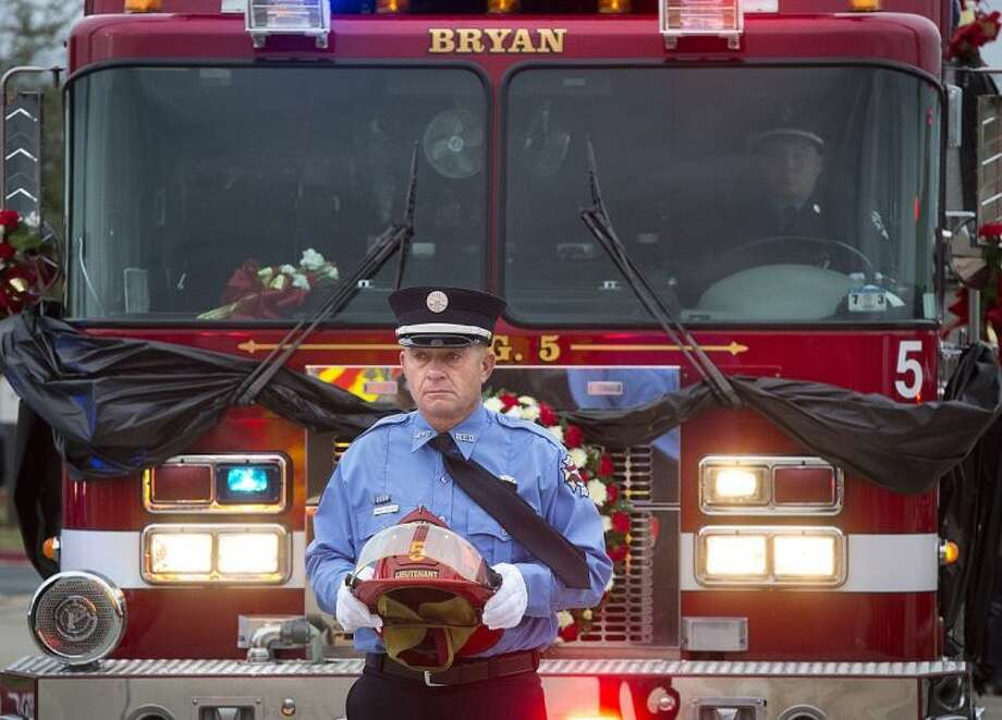 Bryan firefighter Randy Rychlik carries a helmet while walking in a procession at the memorial service for Bryan firefighters Eric Wallace and Gregory Pickard at Central Baptist Church in Bryan Wednesday. Wallace died last Friday fighting a fire at the Knights of Columbus Hall in Bryan. Pickard died the following day in a Galveston hospital from injuries suffered in the same fire. Photo: Stuart Villanueva