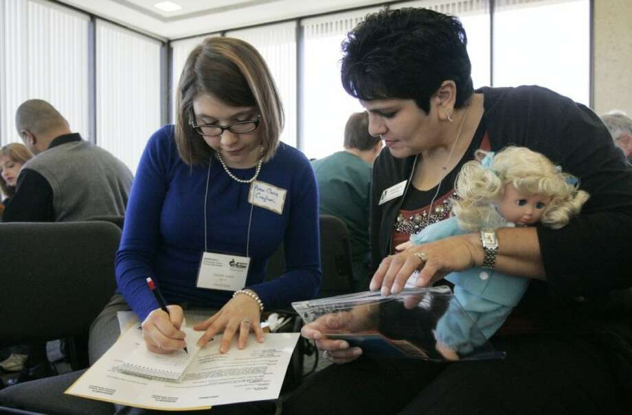 "Anna Claire Croghan, left, and Sonia DeLeon look over their packet with information regarding their ""family's"" situation as they participate in a poverty simulation by TXU Energy and Montgomery County Emergency Assistance Friday, Feb. 25 in Conroe."