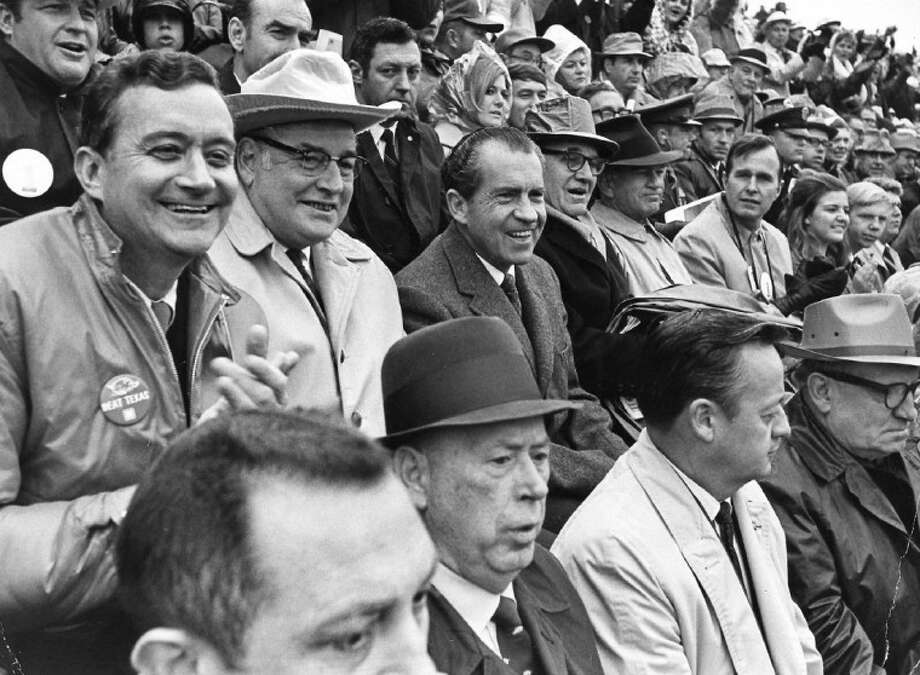 """FILE — In this Dec. 6, 1969, file photo President Richard M. Nixon, center, watches """"The Big Shootout"""" football game between Arkansas and Texas in the stands at Razorback Stadium in Fayetteville, Ark. The NFL, which is trying to maintain its TV blackout of home games that don't sell out, missed an opportunity 40 years ago, 1972, to keep an even more restrictive policy in place when it rebuffed an effort by Nixon to at least televise playoff games. In the row with Nixon, from left, are Rep. John Paul Hammerschmidt, R-Ark., Ark. Gov. Winthrop Rockefeller, Sen. John L. McClellan, D-Ark., Sen. J. William Fulbright, D-Ark., Rep. George H. Bush, R-Tex. Ranked No. 1, Texas won the game and the national championship by defeating No. 2 Arkansas 15-14. Photo: WHITE HOUSE PHOTO"""