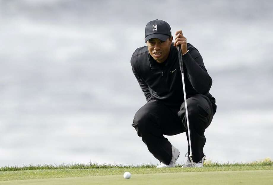 Tiger Woods lines up his putt on the ninth green of the Pebble Beach Golf Links during the third round of the Pebble Beach National Pro-Am golf tournament in Pebble Beach, Calif., Saturday. Photo: Marcio Jose Sanchez