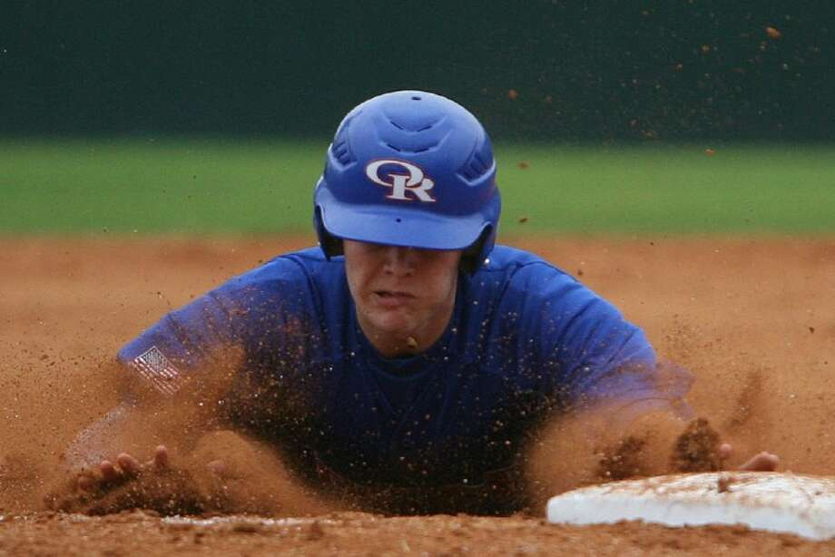 Oak Ridge's Brandon Navarro dives into third base during Saturday's War Eagle Classic game against St. Thomas. Navarro was tagged out before he reached the base on the play.