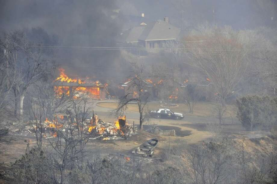 Two homes in the Lake Tanglewood area in Texas burn to the ground as emergency personnel can do nothing but watch Sunday. Texas Forest Service spokesman Lewis Kearney said two wildfires joined about five miles south of Amarillo to destroy or damage almost two dozen homes Sunday afternoon.