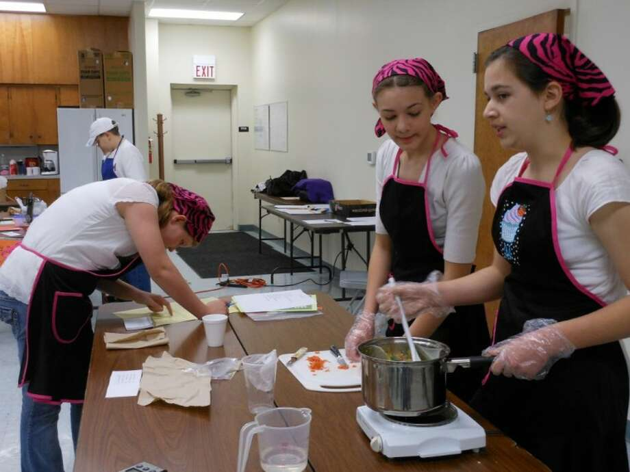 "Team ""Sweet N Salty Girls"" works on a broccoli and carrot mixture to be served with a whole wheat tortilla during Saturday's Montgomery County third annual 4-H Food Challenge."