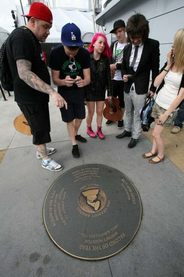 Fans take pictures of a bronze disk honoring Whitney Houston's Record of the Year and Album of the Year in the 36th Grammy Awards, in LA Live before the 54th annual Grammy Awards at the Staples Center on Sunday, Feb. 12, 2012, in Los Angeles. Photo: Ringo H.W. Chiu