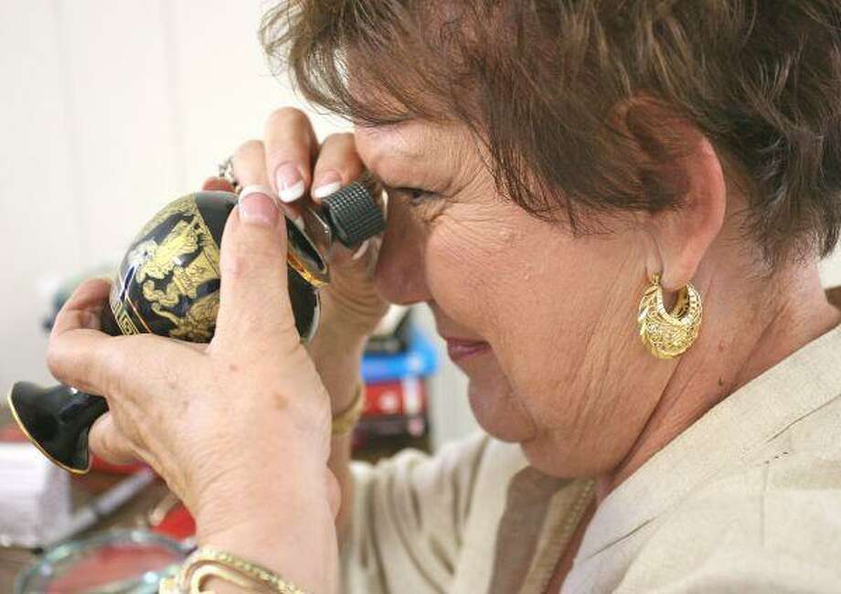 Appraiser Kelly Cook examines an antique vase during Saturday's Historic Montgomery Antique Fair. / The Courier