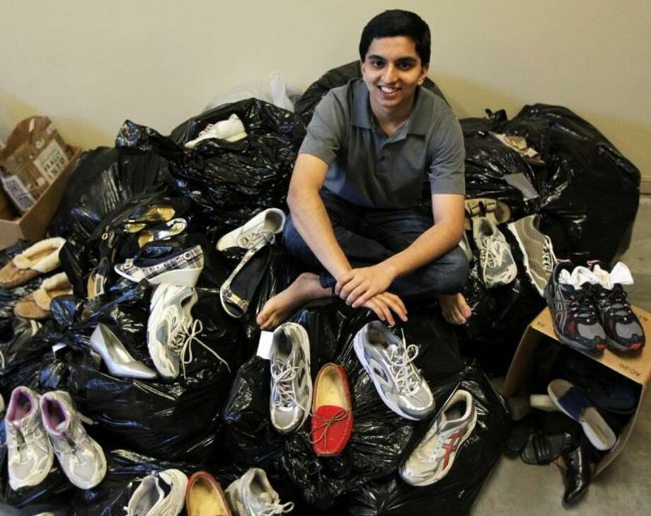 Aarav Chavda poses for a photograph on top of a pile of collected shoes on Feb. 1 in Dallas. Chavda was only 12 when he noticed barefoot children walking on unpaved streets in India. The Dallas native returned from his family trip determined to put shoes on those feet. Photo: Mona Reeder