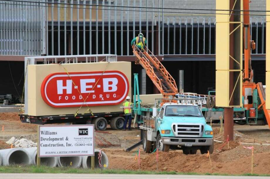 Construction crews erect the sign for the new H-E-B Conroe Market Friday morning.
