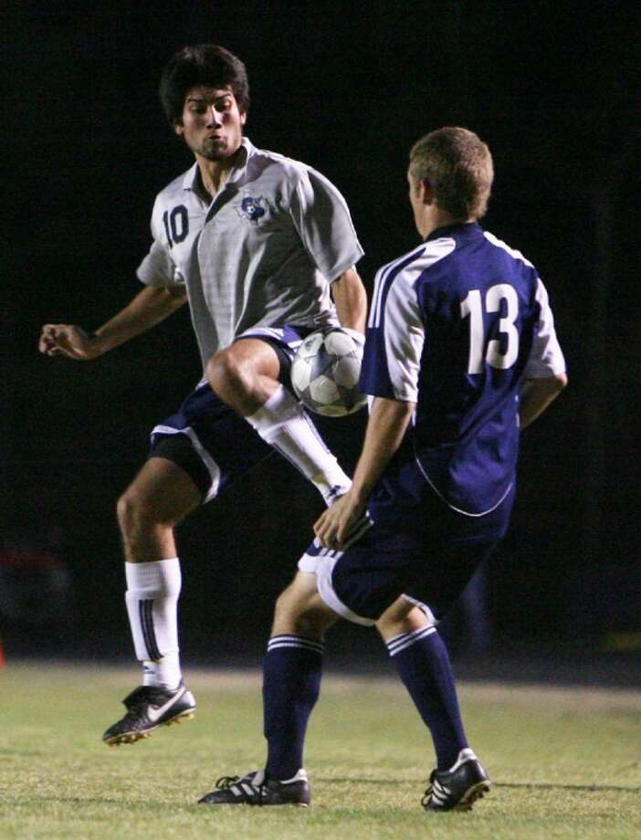College Park's Santiago Montano tries to maintain control of the ball as a Kingwood defender closes in during Tuesday night's District 14-5A game in The Woodlands.