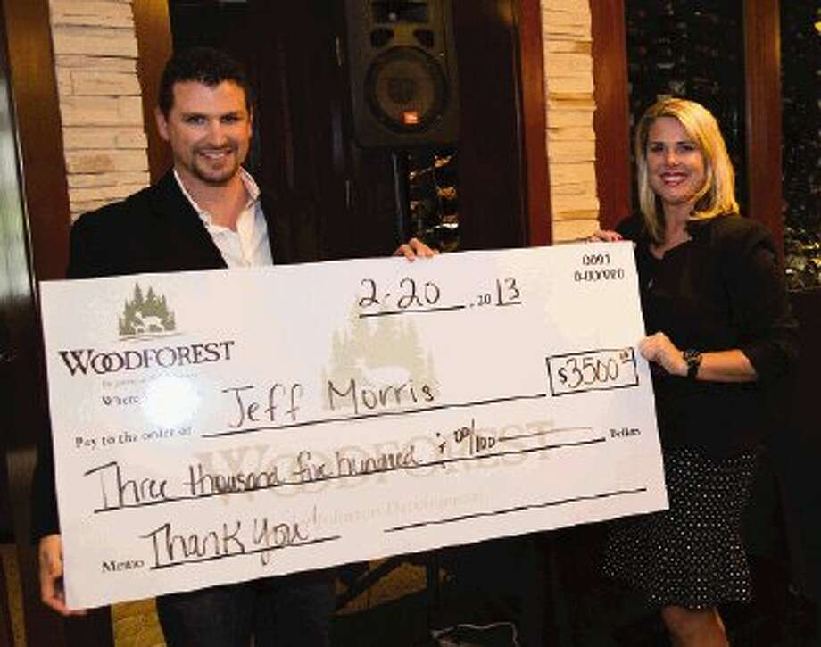 Jeff Morris of RE/MAX Integrity accepts a $3,500 bonus for being the top individual Realtor in Woodforest from Faith Bailes.
