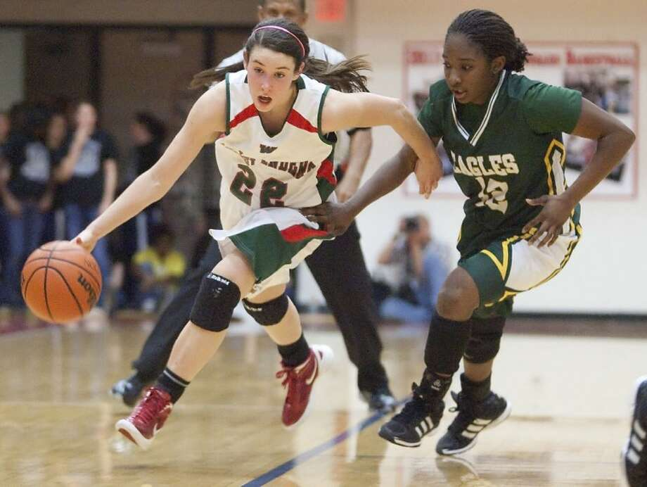 The Woodlands' Paige Bradley dribbles past Klein Forest's Kiera Shephard Tuesday at Tomball High School. See more photos online at www.yourconroenews.com/photos. Photo: Karl Anderson