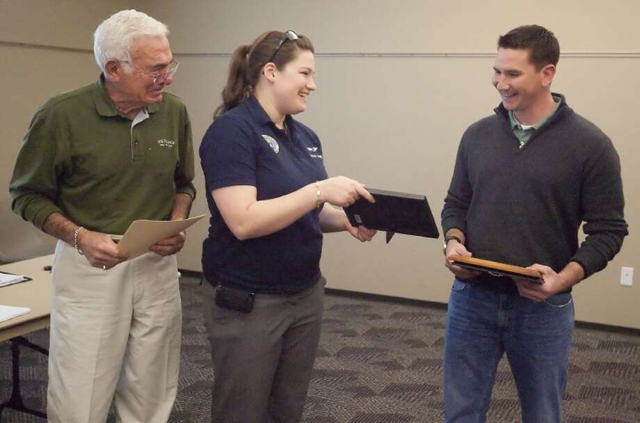 Civil Air Patrol Pilot Sarah Rovner presents air traffic controller Steven Bruce with a drawing to thank him for his help guiding her through a crash landing in downtown Conroe in January during an Airport Advisory Board Meeting Monday at the Lone Star Convention Center in Conroe. Photo: Karl Anderson