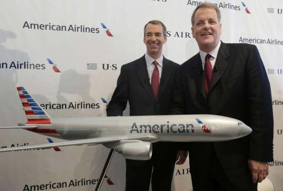 In this Feb. 14, 2013 file photo, U.S. Airways CEO Doug Parker, right, and American Airlines CEO Tom Horton pose after a news conference at DFW International Airport Thursday, in Grapevine, Texas. It wasn't an easy fight, but by the end of this year the 51-year-old Parker will be at the helm of a combined American and US Airways, the world's largest airline. Horton, also 51, will step aside, getting 19.9 million in cash and stock as well as a lifetime of free first class flights, excluding taxes, on American for himself and his wife. Horton will serve as chairman for about a year before stepping down. Photo: LM Otero