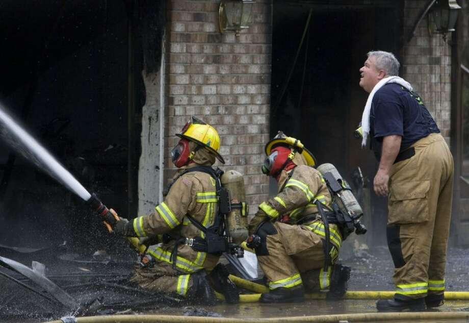 More than 50 firefighters from across Montgomery County battled a three-alarm house blaze Tuesday morning in the Grand Lake Estates subdivision in West Montgomery County. Photo: Staff Photo By Eric S. Swist
