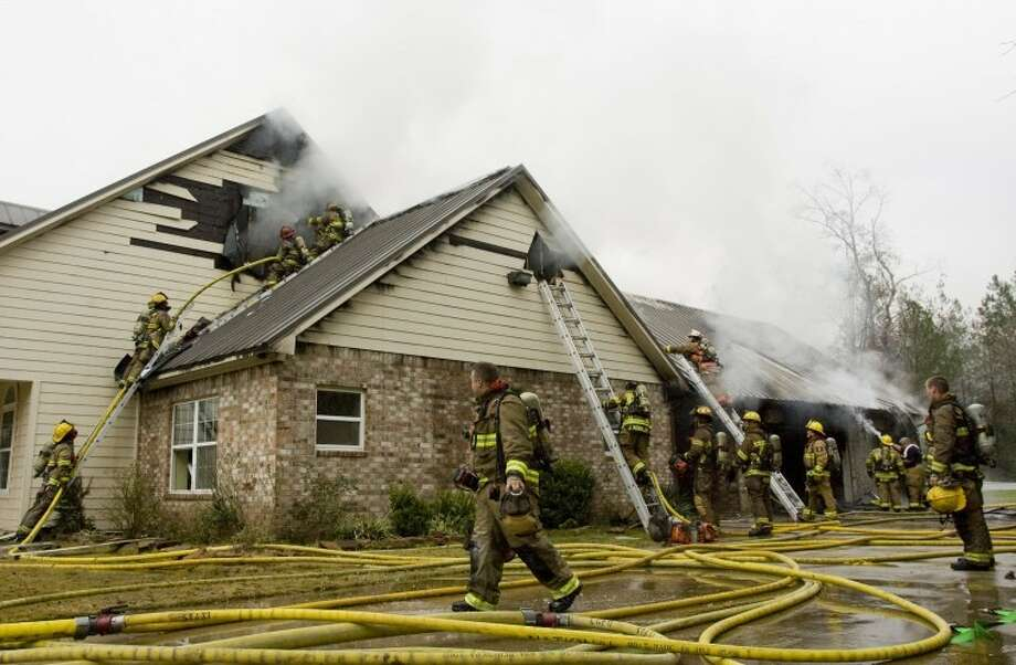 Firefighters work at the scene of a three-alarm fire at a home on 15618 Connie Lane in Magnolia. Photo: Staff Photo By Eric S. Swist