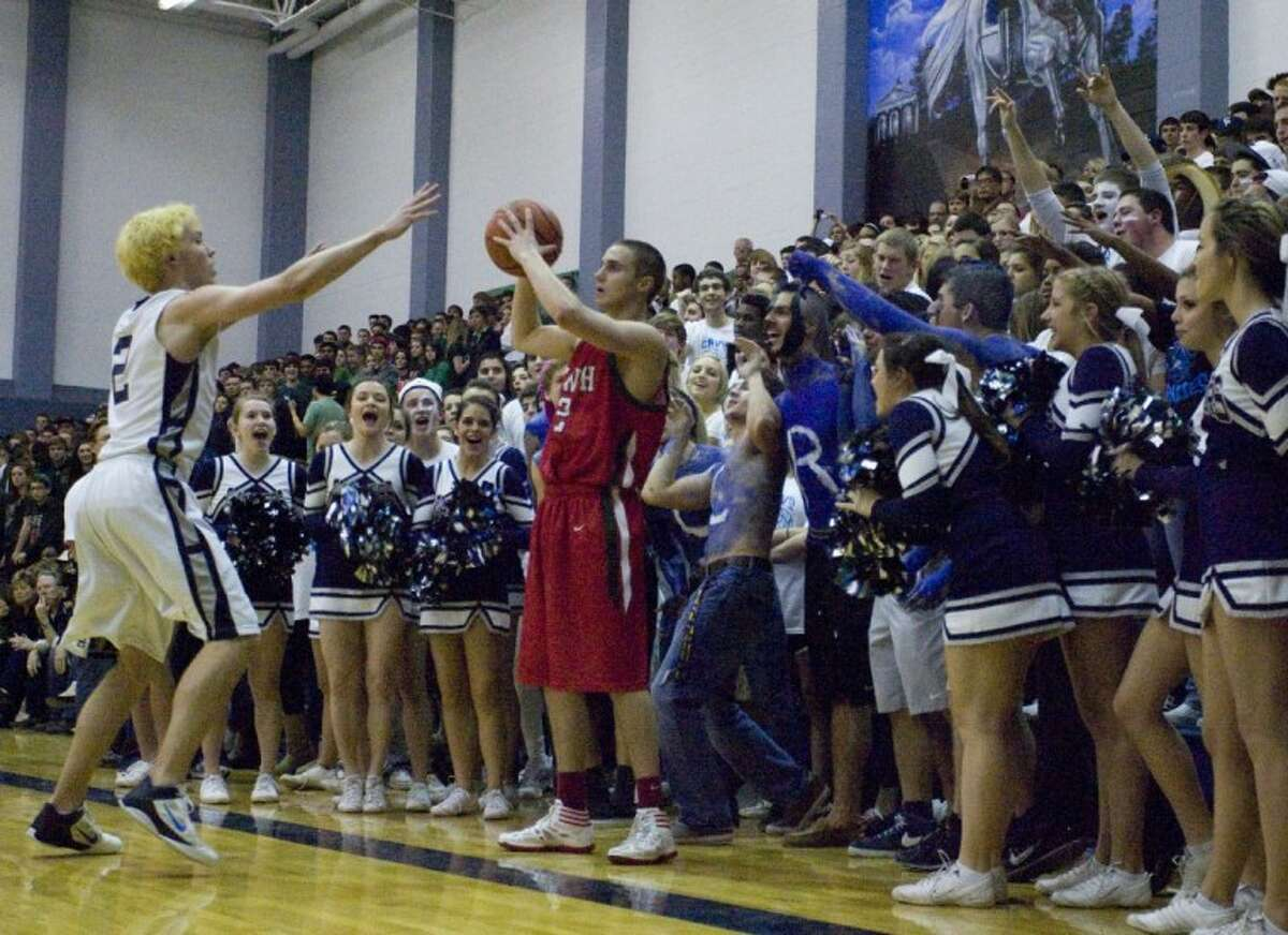 College Park fans taunt The Woodlands' Garret Colonna as inbounds the ball Feb. 10 at College Park High School.
