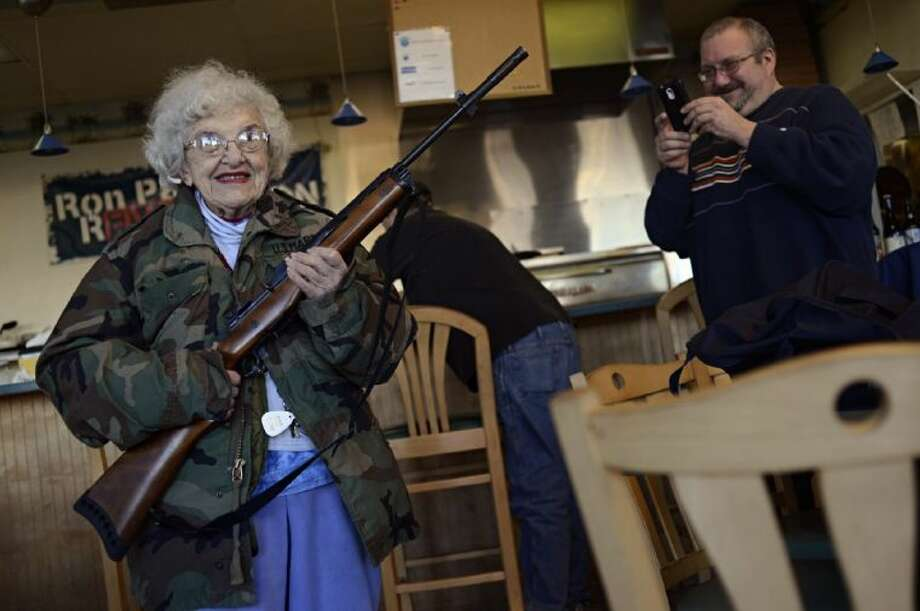 Lee Lazernick, right, asked his mother Thelma Lazernick, left, to pose with a customer's Ruger Mini-14 .223 semi-automatic rifle on Monday, Feb. 18, 2013, at All Around Pizza and Deli in Virginia Beach, Va., where customers wearing weapons or who bring their concealed weapons permit are offered a 15 percent discount. Photo: Amanda Lucier