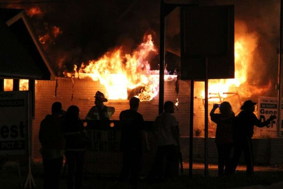 A crowd gathered as flames tore through Williams Furniture in downtown Conroe Monday night. Photo: Photo By James Ridgway, Jr.