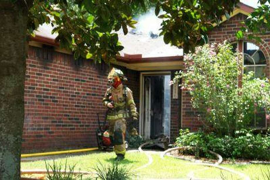 A firefighter exits a Mosswood home that was gutted in a fire Sunday afternoon.