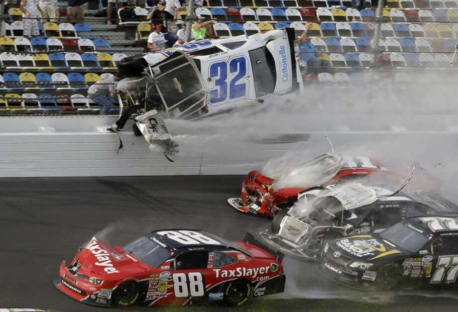 Kyle Larson (32) goes airborne and crashes into the fence in a multi-car crash in the final lap of the NASCAR Nationwide Series race on Saturday in Daytona Beach, Fla. At least 12 fans were injured. Photo: John Raoux