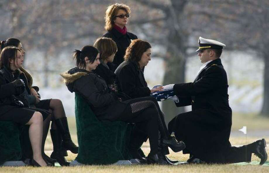 Elisha Vivier, daughter of Raymond Edward Vivier, is presented the U.S. flag by Ensign Haraz Ghanbari, right, during her father's burial services at Arlington National Cemetery Friday in Arlington, Va. Vivier, 61, father of five, had been a homeless man and Marine veteran who rescued five people from the boarding house where he lived before succumbing himself after arsonists set it ablaze. / FR33460 AP