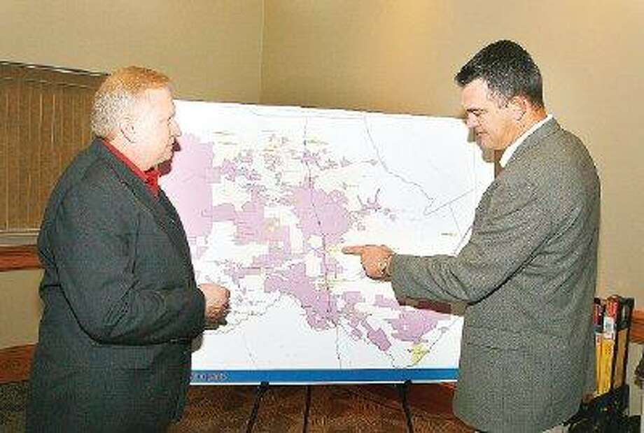Engineering consultant Michael Kennedy, left and Jace Houston, deputy general manager with the San Jacinto River Authority, review a map of Montgomery County reflecting major groundwater users prior to a meeting Friday to discuss state-mandated requirements to develop alternate sources of water.