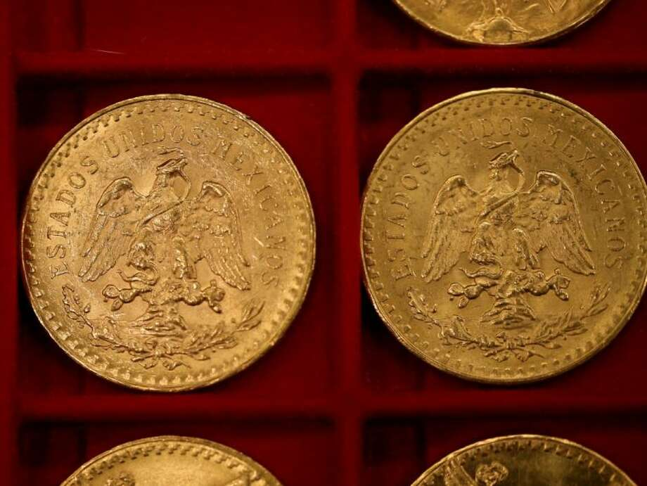 Mexican 50 peso pieces were among the 3.5 million in gold coins auctioned off in Carson City, Nev., on Tuesday, Feb. 26, 2013. Recluse Walter Samaszko died in June 2012, leaving thousands of coins hidden in his garage. (AP Photo/Las Vegas Review-Journal, Cathleen Allison) Photo: Cathleen Allison