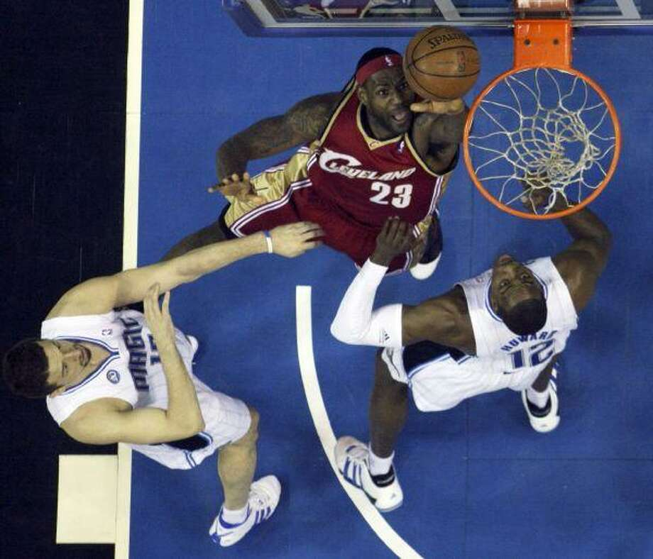 Cleveland's LeBron James makes a shot over Orlando Magic forward Hedo Turkoglu, left, and center Dwight Howard in the first half of Game 3 of the NBA Eastern Conference Finals in Orlando, Fla., Sunday. / FR156687 AP