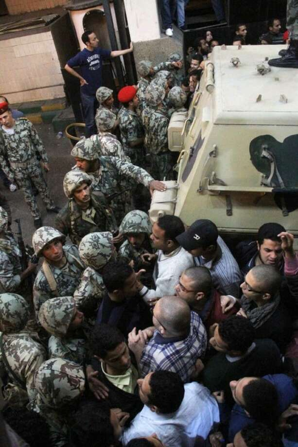 Egyptian soldiers, left, are unsuccessful as they try to stop angry protesters who storm the state security building headquarters in Cairo's northern Nasr City neighborhood, Egypt, Saturday.