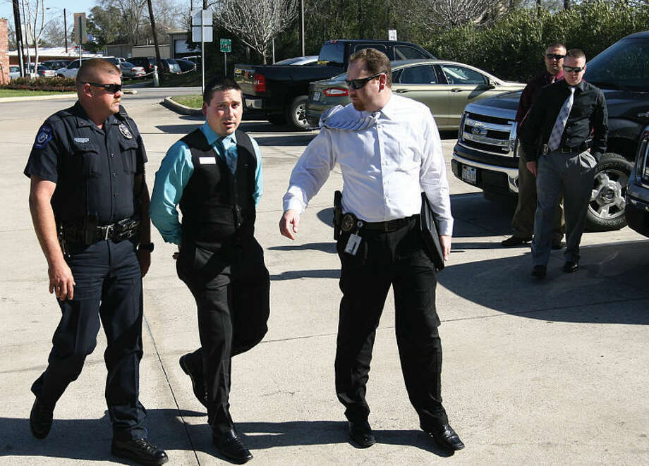 UIL referee Brian Joseph Ortiz was escorted into the Conroe Police Department Monday, charged with second-degree felony of improper relationship between an educator and a student, stemming from an alleged relationship with an 18-year-old male student at Caney Creek High School. He was escorted into the Police Department by Officer Leigh Landriault, left, and Detective Ben Mitchell. Photo: Staff Photo By Brad Meyer