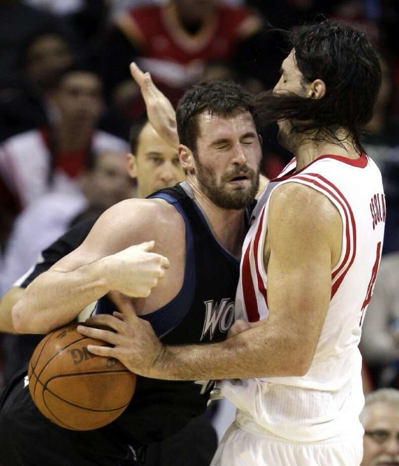 Minnesota Timberwolves' Kevin Love, left, charges into Houston Rockets' Luis Scola, right, during the third quarterFriday in Houston. Photo: David J. Phillip