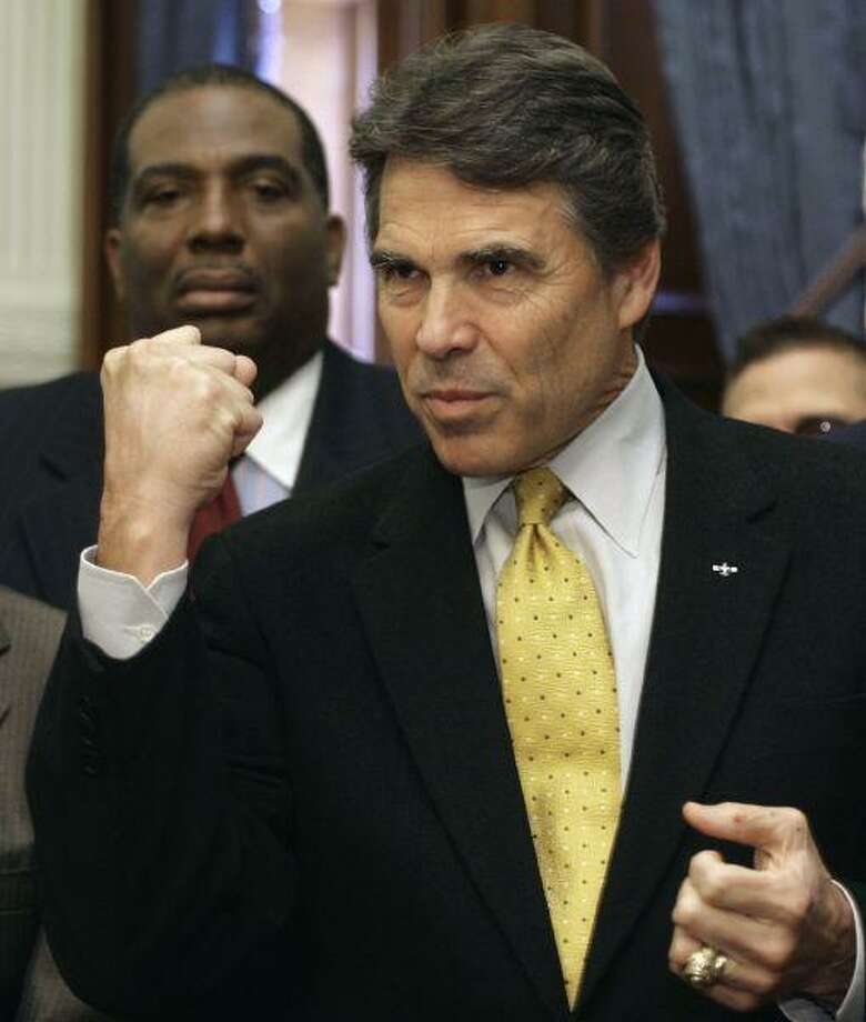 Texas Gov. Rick Perry pumps a fist as he speaks during a bill-signing ceremony in his Reception Room Wednesday in Austin. Earlier, Gov. Perry met privately with House Speaker Joe Straus in an attempt to salvage major legislation this session after partisan fighting slowed down work in the House. Sen. Royce West, D-Dallas, is on the left. / AP
