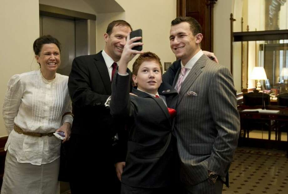 Carson Schwertner, 13, takes a photo of himself with Texas A&M Heisman Trophy-winning quarterback Johnny Manziel at the Capitol in Austin on Feb. 6. Both the Texas House and the Senate passed resolutions congratulating the football star. Carson is the son of State Sen. Charles Schwertner, R-Georgetown, and Belinda Schwertner, left. Photo: Jay Janner