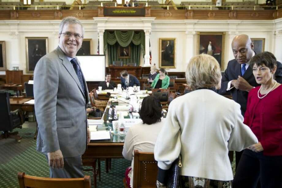 Former Florida Gov. Jeb Bush, left, gets ready to speak at the Senate Education Committee meeting at the Capitol in Austin on Wednesday. Bush urged Texas to swing for the fences when overhauling public education, telling state senators Wednesday that he was able to transform foundering schools in his home state with big, if often unpopular, ideas. Photo: Jay Janner