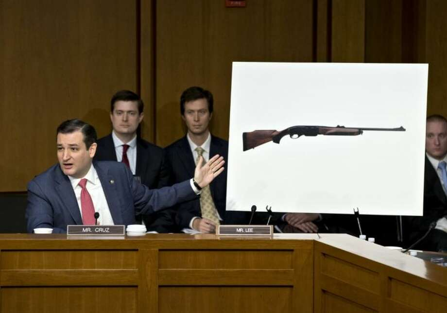 In this Jan. 30, 2013 file photo Sen. Ted Cruz, R-Texas, points to a life size photo of a Remington 750, a popular hunting rifle, to make a point about the proposed ban on certain kinds of guns during a Senate Judiciary Committee on Capitol Hill in Washington.