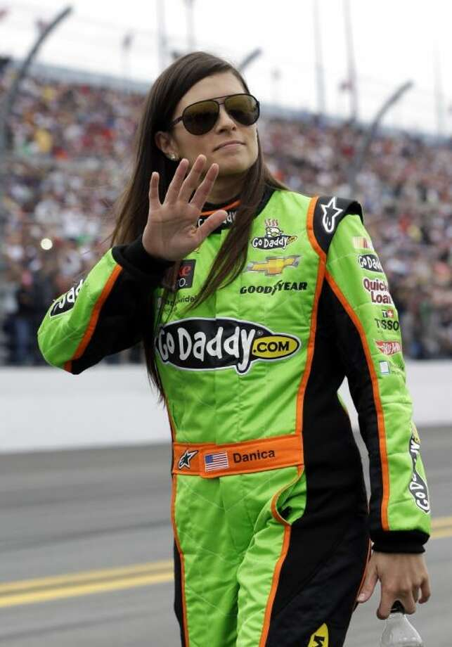Danica Patrick waves to fans as she walks down pit road before the Daytona 500. Patrick finished eighth in the race. Photo: John Raoux