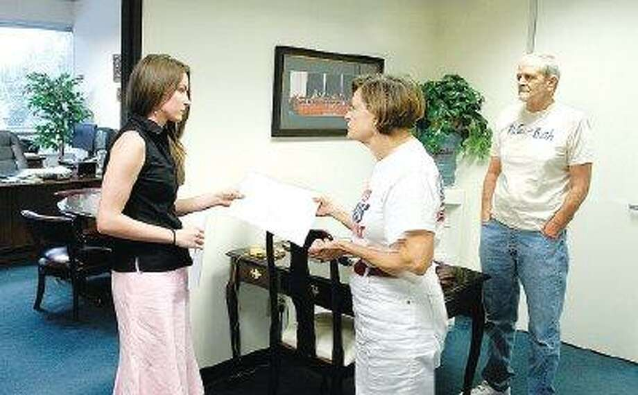 Christine Reese, left, a staff member for U.S. Rep. Kevin Brady, R-The Woodlands, accepts a petition from Montgomery County residents Carol Stromatt and Craig Bubier calling for development of a long-range national energy policy that is less reliant on foreign oil and focuses on clean, renewable types of energy.