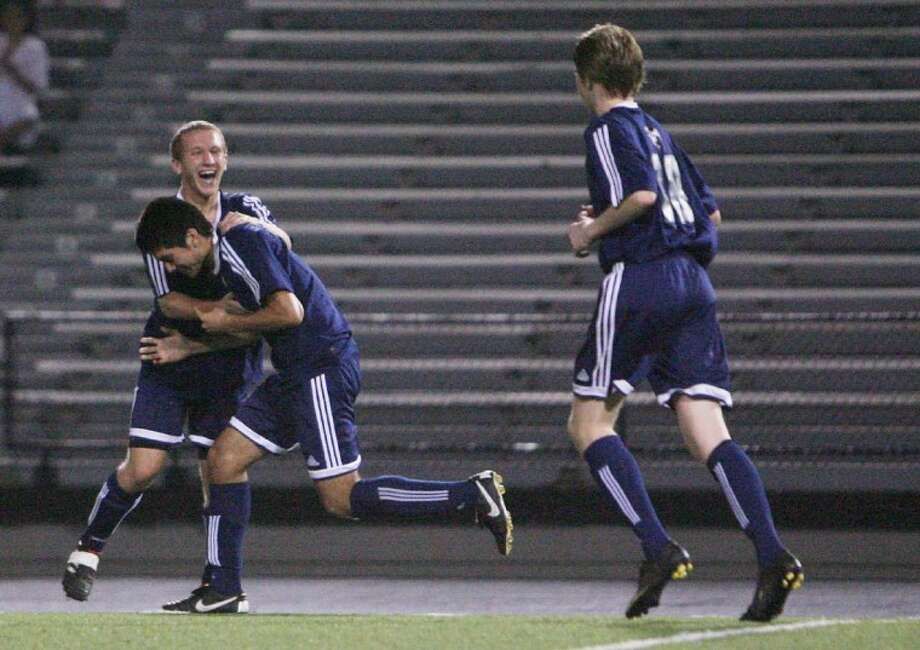 College Park's Santiago Montano, middle, and Matt Ruhe, far left, celebrate a goal in the first half of Tuesday night's game against Conroe.