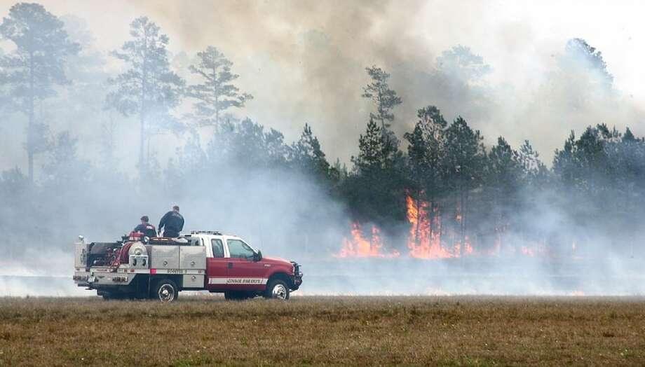 Wind gusts in excess of 30 mph Monday afternoon spread a massive fire to wooded areas around Lone Star Executive Airport, threatening nearby residential areas.