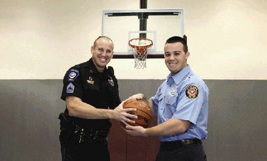 Conroe Police Department Sgt. Brent Stowe, left, and firefighter Michael Hill prepare for the city's first SlamFest 3-on-3 basketball tournament Saturday.