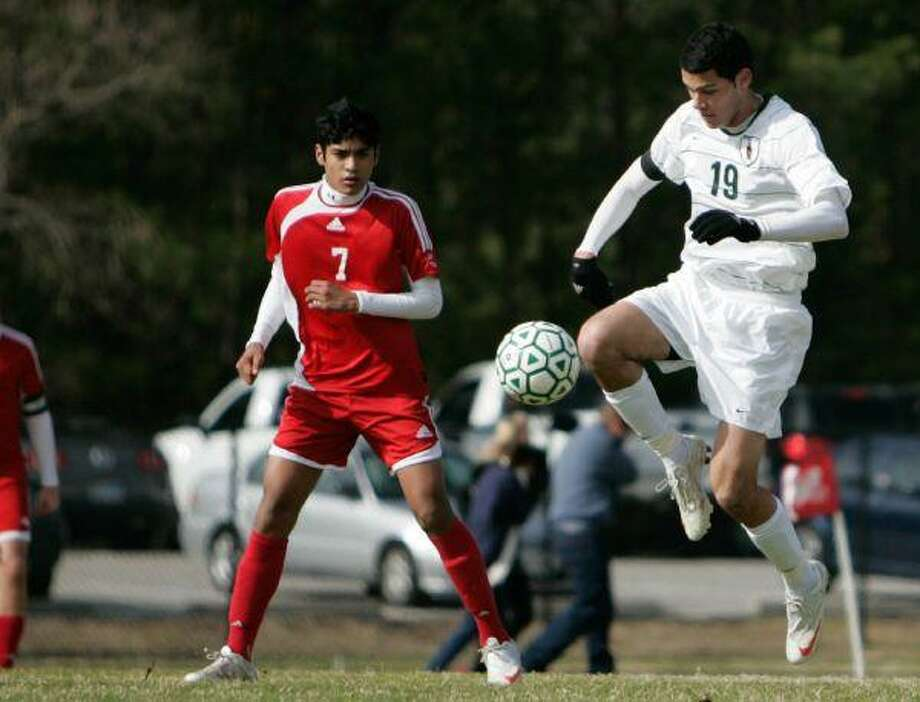 The Woodlands midfielder Sebastian East tries to maintain control of the ball as Dulles defender Keven Chumbiray (7) closes in during Thursday's cold-weather Kilt Cup tournament soccer game at The Woodlands High School. For details on the game, see Page 1B in Sports. / The Courier