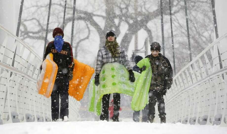 Chance Cain, from left, Simon Mourning and Nathan Talley walk toward a sledding hill near downtown Wichita, Kan. as a winter storm moves through the area on Monday, Feb. 25, 2013. Photo: Travis Heying