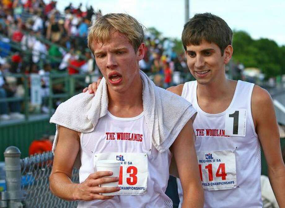The Woodlands High School's Drew Butler, left, and Reed Connor rest after competing in the 1,600, Saturday during the Region II-5A track and field meet in Waco. / The Courier