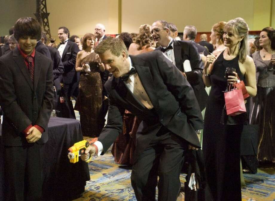 John Horton shoots a Nerf gun at a stack of cans Saturday at the Montgomery County Heart Ball at The Woodlands Waterway Marriott. Photo: Staff Photo By Eric S. Swist