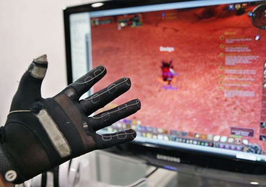 An attendee uses Iron Will Innovations' glove game controller with a video game at the Consumer Electronics Show (CES) in Las Vegas last week. / AP