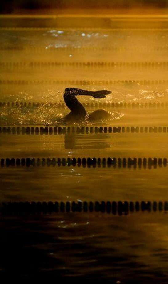 Cyndi Perkins swims through steamy waters on a chilly morning at the Bryan Aquatic Center. / AP2010
