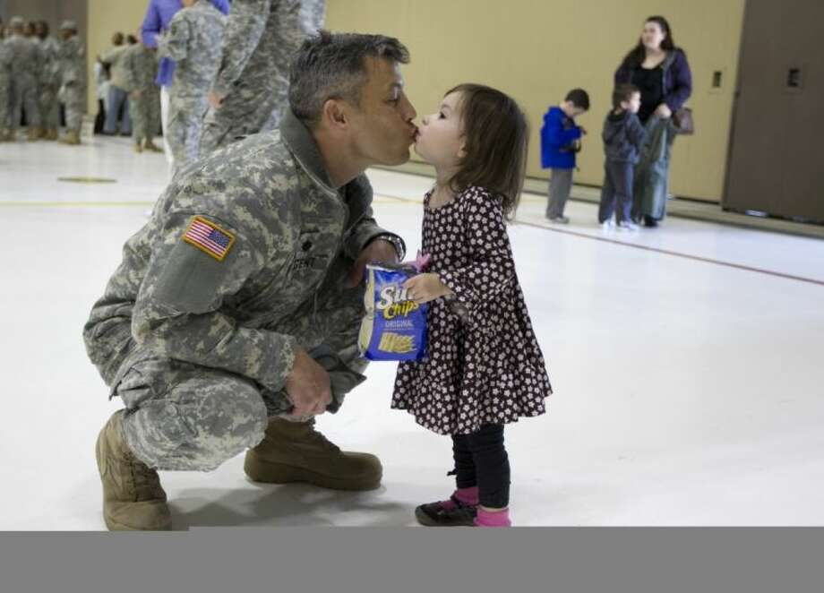 Lt. Col. Jim Nugent of the Texas Army National Guard 36th Infantry Division kisses his daughter, Sienna Nugent, 23 months old, after a deployment ceremony at the Austin Army Aviation Support Facility in Austin on Wednesday. Photo: Jay Janner